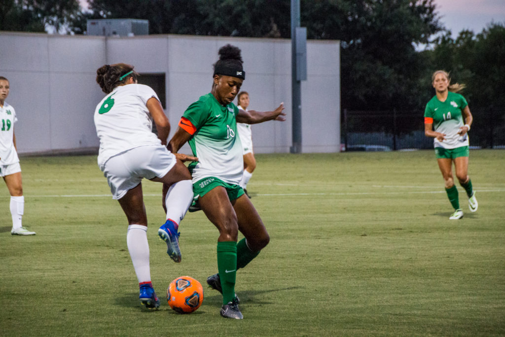 North Texas senior forward Rachel Holden (16) sneaks the ball under a Marshall defender during a game on September 22. Holden has started every game she's played over the past four years for the Mean Green. Dylan Nadwodny