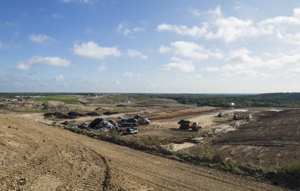 Dump trucks back their loads into the waste landfill in Denton. This is one of five cells within the 700-acre footprint at the Denton Landfill where the team is preparing to mine methane. Hannah Breland