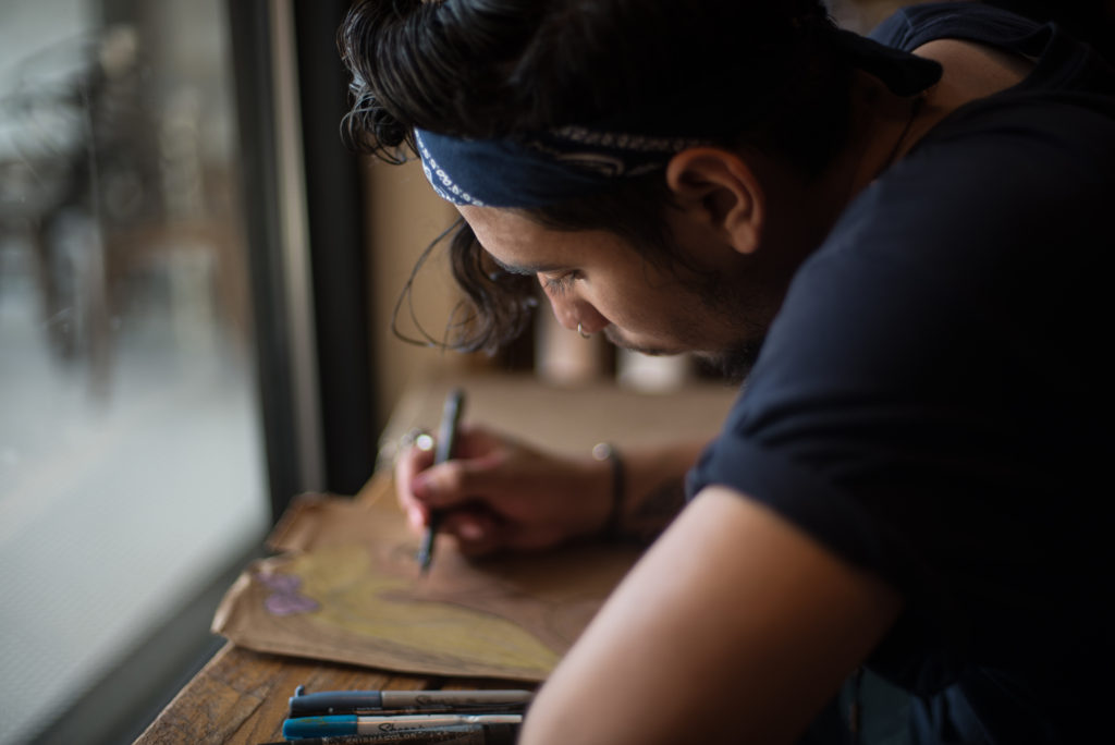 Kailon Medrano, 20-year-old Denton resident, works on one of his art pieces at West Oak Coffee Bar. Hannah Breland