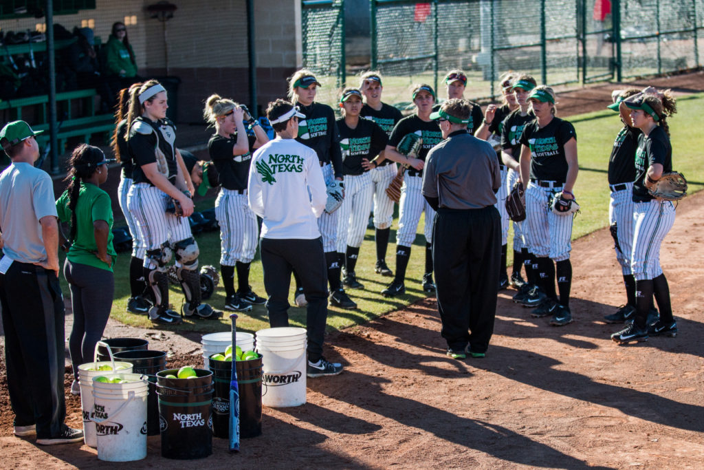 The North Texas softball team gathers around head coach Tracey Kee as she recaps the first drill of practice and goes over the next. Dylan Nadwodny