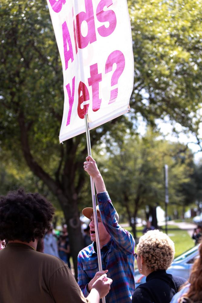 "A protester holding a ""Got Aids Yet?"" sign yells over a crowd of students."