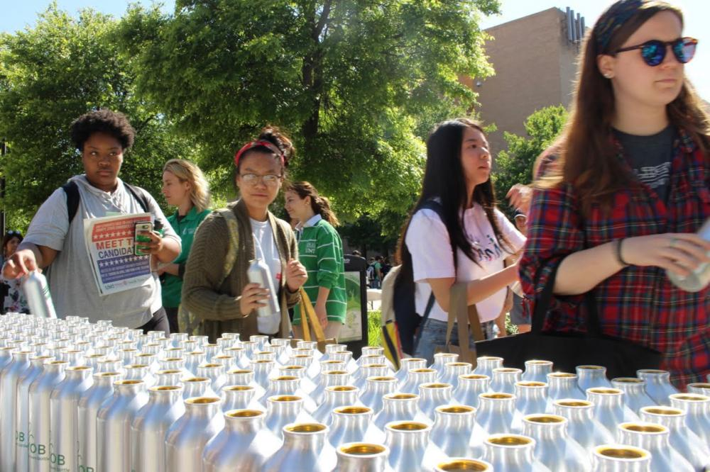 Students pick up a free bottle at Earth Fest Thursday evening.